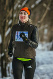 Smiling middle-aged women run. Ekaterinburg, Russia - November 14, 2015: smiling middle-aged woman with headphones running winter forest during Urban winter stock images