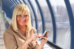 Smiling middleaged woman with pda Royalty Free Stock Photos