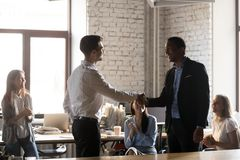 Businessman handshake male employee congratulating with success. Smiling millennial businessman shake hand of male colleague congratulating with success or royalty free stock photography