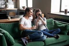 Smiling couple watching mobile video online sitting on home sofa. Smiling millennial couple enjoying watching mobile video on phone sitting on sofa at home Stock Images