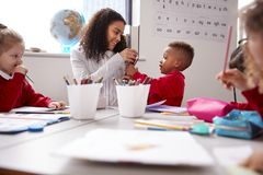 Smiling millennial female infant school teacher sitting at table with kids in a classroom giving pencils to a schoolboy, low angle royalty free stock photo