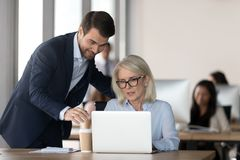 Smiling millennial manager help mature woman with laptop royalty free stock images