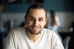 Smiling millennial man looking at camera in cafe, headshot portr. Smiling young men with attractive face head shot portrait, happy handsome millennial guy Royalty Free Stock Photo