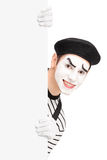 A smiling mime artist posing behind a blank panel Stock Photos