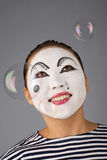 Smiling mime portrait blowing bubbles Stock Photography