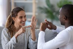 Smiling mixed ethnicity couple talking with sign finger hand language