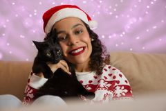 Mixed race girl with christmas hat and domestic cat pet. decoration with colorful lights stock photos