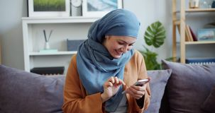 Smiling mixed race girl in hijab using smartphone touching screen at home. Smiling mixed race girl in hijab is using smartphone touching screen sitting on couch stock footage