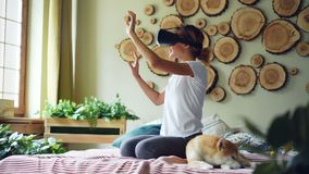 Smiling mixed race girl is using augmented reality glasses moving hands sitting on bed in modern apartment with adorable. Dog beside her. Technology, youth and stock footage