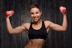Smiling mixed race sporty woman holding dumbbells Royalty Free Stock Photos