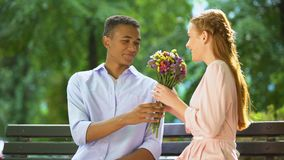 Smiling mixed-race teen boy presenting beloved girl flowers, first date in park. Stock footage stock footage