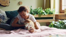 Smiling mixed race teenager is taking selfie with puppy then talking to it and showing it photos on smartphone screen. Smiling mixed race teenager is taking stock footage