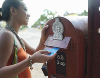 Smiling Mixed Race Woman Putting Postcard In Mailbox Stock Images