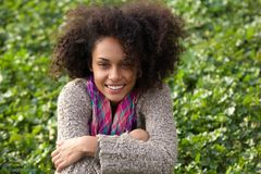 Smiling mixed race woman sitting on grass Stock Photos