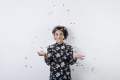 Smiling mixed race woman throwing confetti. Indoors Stock Photo