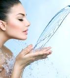 Smiling model girl under splash of water. Beautiful smiling model girl under splash of water over blue Stock Photos