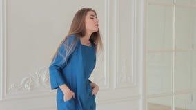Smiling model posing in blue dress in studio stock footage
