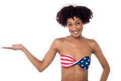Smiling model in stars and stripes bikini presenting copy space Royalty Free Stock Image