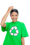 Smiling model wearing recycling tshirt holding light bulb above Royalty Free Stock Photography