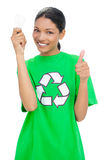 Smiling model wearing recycling tshirt holding light bulb Stock Photography
