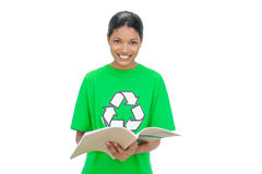 Smiling model wearing recycling tshirt holding notebook Royalty Free Stock Photos
