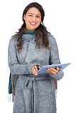 Smiling model wearing winter clothes holding her tablet Stock Images