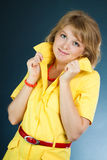 Smiling model in a yellow dress. On a dark background (studio work Stock Images