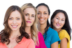 Smiling models in a line posing with colorful t shirts royalty free stock photography