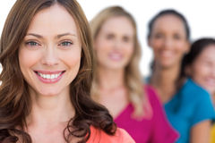 Smiling models in a line posing with focus on brunette Stock Photography