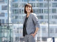 Smiling modern business woman standing in the city Stock Images