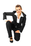 Smiling modern business woman standing on one knee Royalty Free Stock Photography