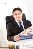 Smiling modern businessman holding newspaper Royalty Free Stock Photos