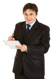 Smiling modern businessman making notes in notepad Royalty Free Stock Photos