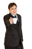 Smiling modern businessman offering cup of coffee Stock Image