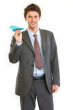 Smiling modern businessman with paper airplane Royalty Free Stock Photography