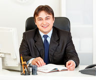 Smiling modern businessman sitting at office desk Royalty Free Stock Images
