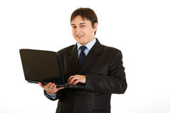 Smiling modern businessman using laptop Stock Image