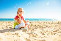 Smiling modern child in colorful shirt on beach blowing bubbles Royalty Free Stock Images