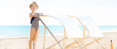 Smiling modern child in swimsuit on beach near beach chair Royalty Free Stock Photos