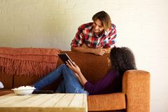 Smiling modern couple relaxing at home with digital tablet Stock Image