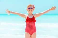 Smiling modern girl with sun screen rejoicing on seacoast stock photography