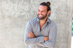 Smiling modern man with beard standing with arms crossed royalty free stock photography