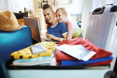 Smiling modern mother and child planning trip online. Smiling modern mother and child in the modern living room in sunny summer day planning trip online royalty free stock photos