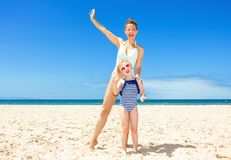 Smiling modern mother and child on seashore having fun time Royalty Free Stock Photography