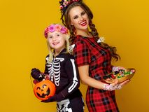 Smiling modern mother and daughter with Halloween candies Royalty Free Stock Photo