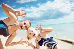 Smiling mother and daughter on seashore showing empty palms. Smiling modern mother and daughter in swimsuit on the seashore showing empty palms stock photography