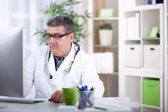Smiling modern senior doctor with glasses in the office Stock Photography