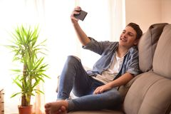 Teen taking a selfie sitting on a couch in the living room. Smiling modern teenager taking a selfie sitting on a sofa in the living room of his house Stock Photos