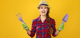 Smiling modern woman farmer showing gardening tools. Healthy food to your table. Portrait of smiling modern woman farmer in checkered shirt isolated on yellow Stock Photo