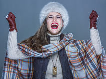 Smiling modern woman in fur hat isolated on cold blue rejoicing Stock Photos